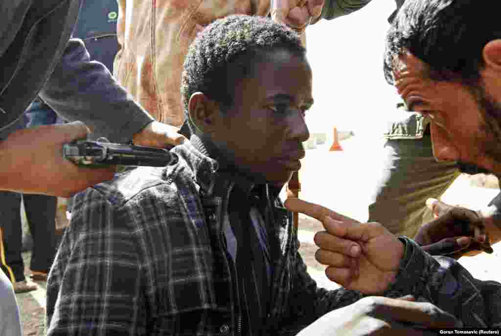 "Rebels question an African man in Libya in March 2011. Tomasevic later told The New York Times that ""when I photographed a young man suspected of being a mercenary because of his skin color, I felt terrified for him."""