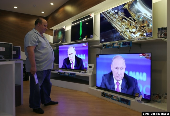 A man in an electronics shop in Moscow watches Russian President Vladimir Putin's televised question-and-answer session on June 15.