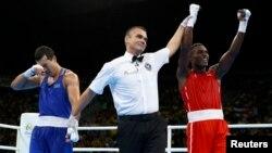 Казахстанский боксер Адильбек Ниязымбетов (слева) в момент, когда рефери объявляет победителем финального боя кубинца Хулио Сесара Ла Круса (справа). Рио-де-Жанейро, 18 августа 2016 года.