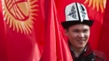A man wearing the Kyrgyz national hat poses with national flags before a rally marking the Day of Flag and the Day of Kalpak in Bishkek in March 2013.