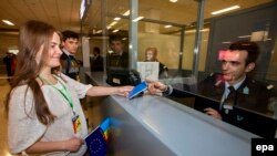A Moldovan woman presents her passport at the Athens International Airport.