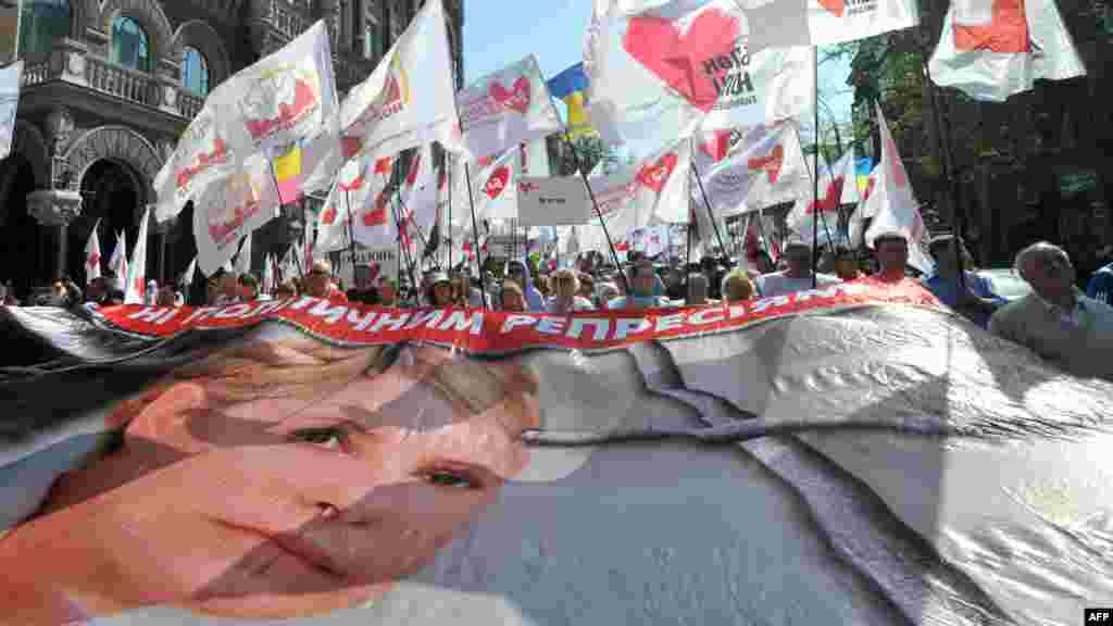 Tymoshenko supporters carry a huge poster featuring her during a rally of the opposition in Kyiv on April 27, 2012.