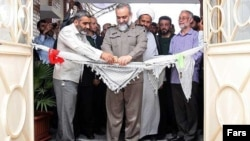 Mohammad Reza Naghdi, commander of Iran's Basij militia, cuts the keffiyehs at an opening ceremony for Basij cultural works.