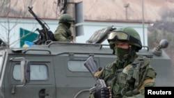Вооруженные люди рядом с российскими военными автомобилями в крымском городе Балаклава. 1 марта 2014 года.