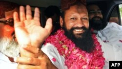 Lashkar-e Jhangvi leader Malik Ishaq waves to supporters in Lahore on July 14.