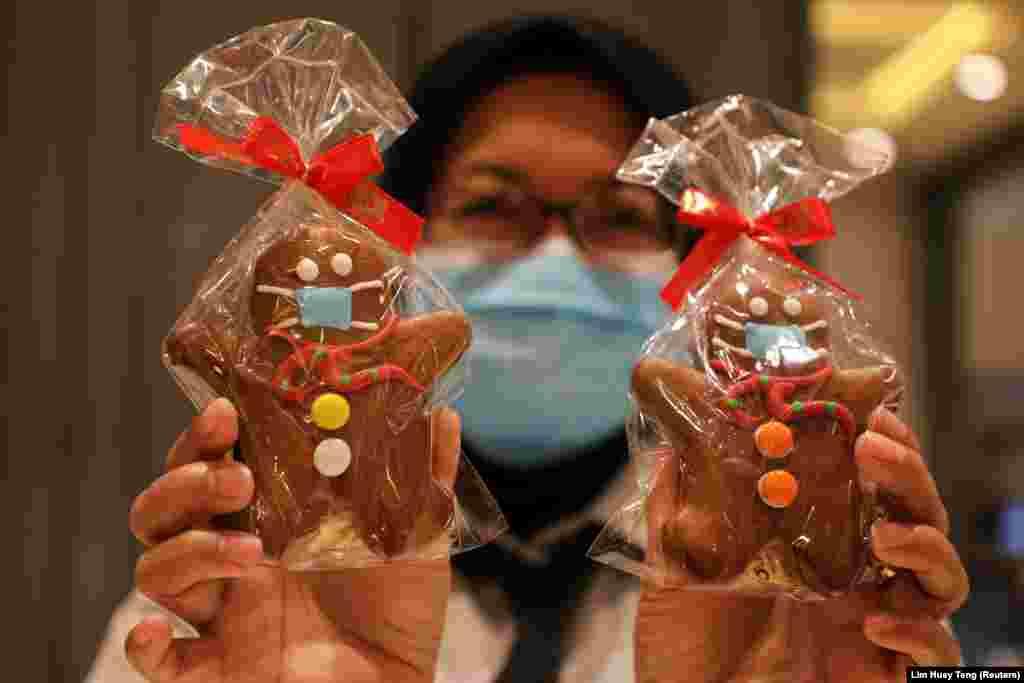 Продавец держит пряничных человечков в защитных масках для празднования Рождества в пекарне в Куала-Лумпуре, Малайзия, 4 декабря 2020 года
