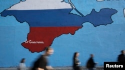 Russia -- People pass a mural showing a map of Crimea in the Russian national colours on a street in Moscow, March 25, 2014. Russia's annexation of Crimea has piqued interest in the region's Tatar community.