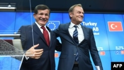 Turkish Prime Minister Ahmet Davutoglu (left) smiles with European Council president Donald Tusk during a press conference at the end of a summit on relations between the European Union and Turkey and on the migrant crisis at the European Council in Brussels.