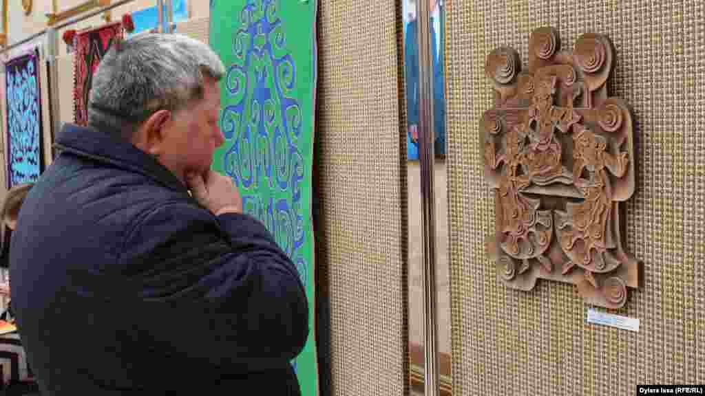 Посетитель выставки рассматривает изделия ремесленников. Мастера привезли продукцию из дерева, кости, войлока, кожи, металла.