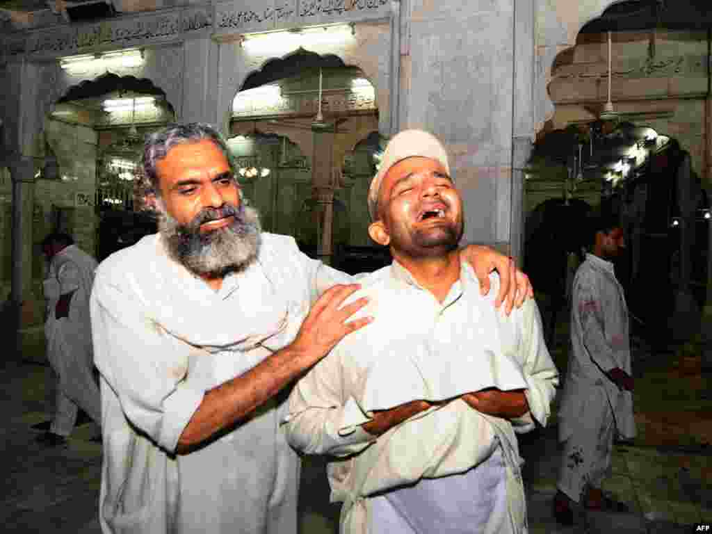 A Pakistani devotee comforts a man at the site of a double suicide bombing at a Sufi shrine in Lahore on July 2. At least 40 people were killed and more than 120 wounded at the shrine, the tomb of Sufi saint Data Gunj Bakhsh. Photo by Arif Ali for AFP