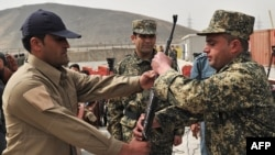 A Blue Hackle officer (left) hands over a gun to a soldier from the Afghan Public Protection Forces during a ceremony on the outskirts of Kabul in March.