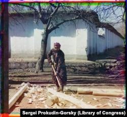 Плотник снимает кору со свежесрубленного дерева на проселочной дороге в Самарканде