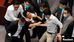 Күзетшілер демократтардың бірін парламент залынан күштеп шығарып жатыр. Гонконг, 18 мамыр 2020 жыл.