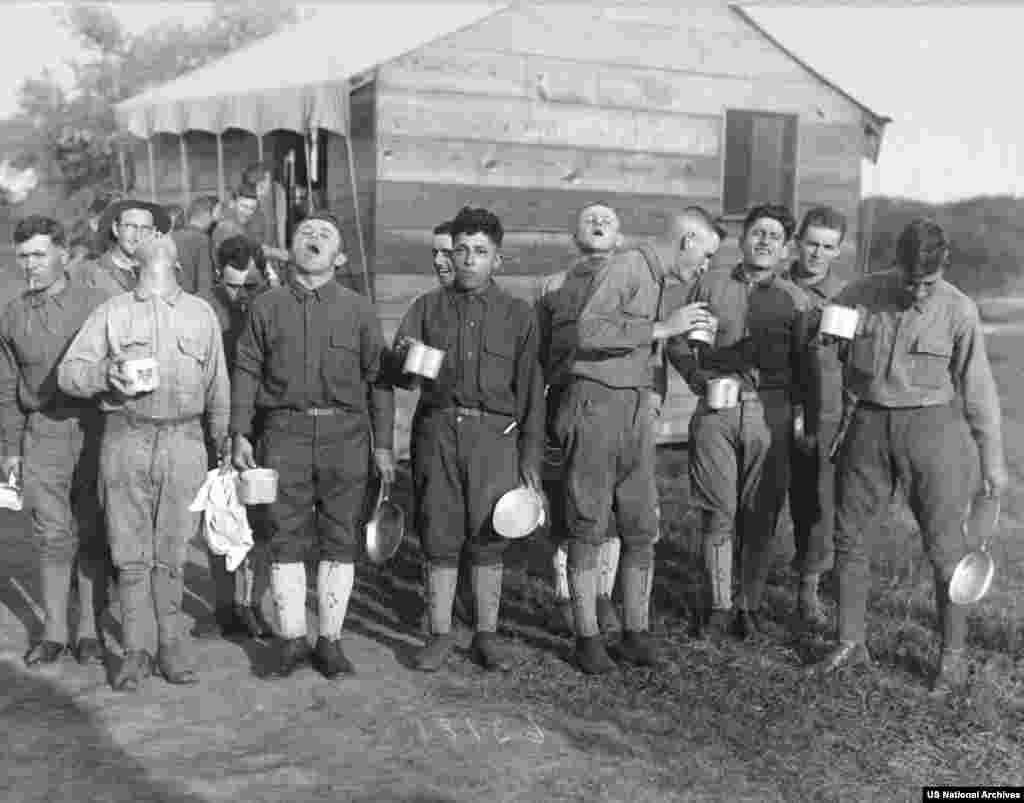 """Мъже от американска военна база си правят гаргара със солена вода - една от многото съмнителни """"превантивни мерки"""" срещу разпространението на вируса."""