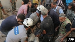 Syrian civil-defense volunteers, known as the White Helmets, hold the body of a young man after he was pulled from the rubble following a government air strike on the rebel-held neighborhood of Karm Homad in the northern city of Aleppo on October 4.