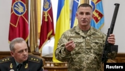 Представитель министерства обороны Украины показывает на пресс-конференции оружие, которое, как он утверждает, было изъято у двух мужчин, предположительно российских военнослужащих, задержанных на востоке страны. Киев, 18 мая 2015 года.