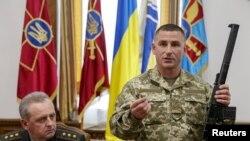 Украинские военные показывают снайперскую винтовку, которой были вооружены пленные