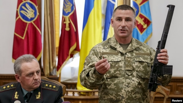 A Ukrainian military commander (right) shows a rifle seized from Russian soldiers as Colonel General Viktor Muzhenko, chief of the General Staff and commander-in-chief of the armed forces of Ukraine, looks on during a news conference in Kyiv on May 18.