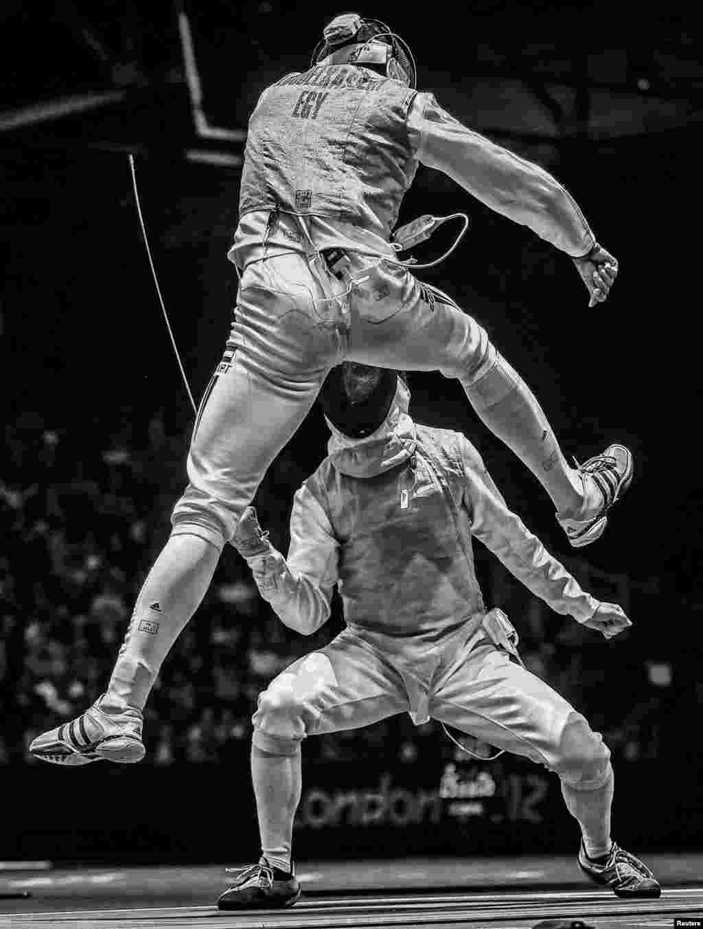 """Sergei Ilnitsky of Russia, a photographer working for the European Pressphoto Agency, won second prize in the Sports Action Stories category with the series """"The Golden Touch -- Fencing at the Olympics."""" This picture shows Alaaeldin Abouelkassem of Egypt (top) in action against Peter Joppich of Germany during their Men's Foil Individual round 16 bout at the 2012 Olympic Games in London."""