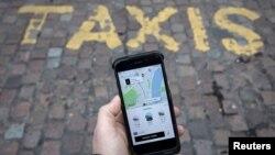 Një udhëtar duke përdorur aplikacionon Uber në rrugët e Londrës