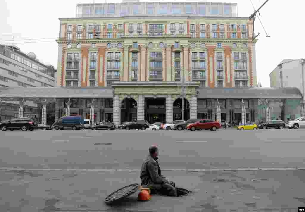 A municipal worker sits in a manhole in front of the Ritz-Carlton hotel in Moscow. (epa/Maxim Shipenkov)
