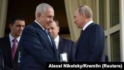 Presidenti rus, Vladimir Putin (djathtas) derisa takon kryeministrin izraelit, Benjamin Netanyahu në një takim në Soçi në gusht të vitit të kaluar.