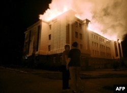 Прохожие смотрят, как горит здание школы. Донецк, 27 августа 2014 года.