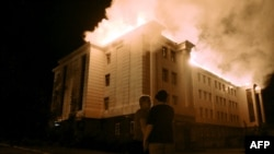 Bystanders watch a fire consuming a school in the eastern Ukrainian city of Donetsk on August 27.