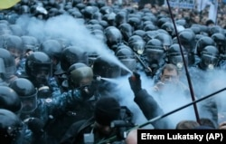 On November 24, the first clashes took place in front of the Ukrainian government building in Kyiv. In this image, protesters and riot police spray tear gas at each other.