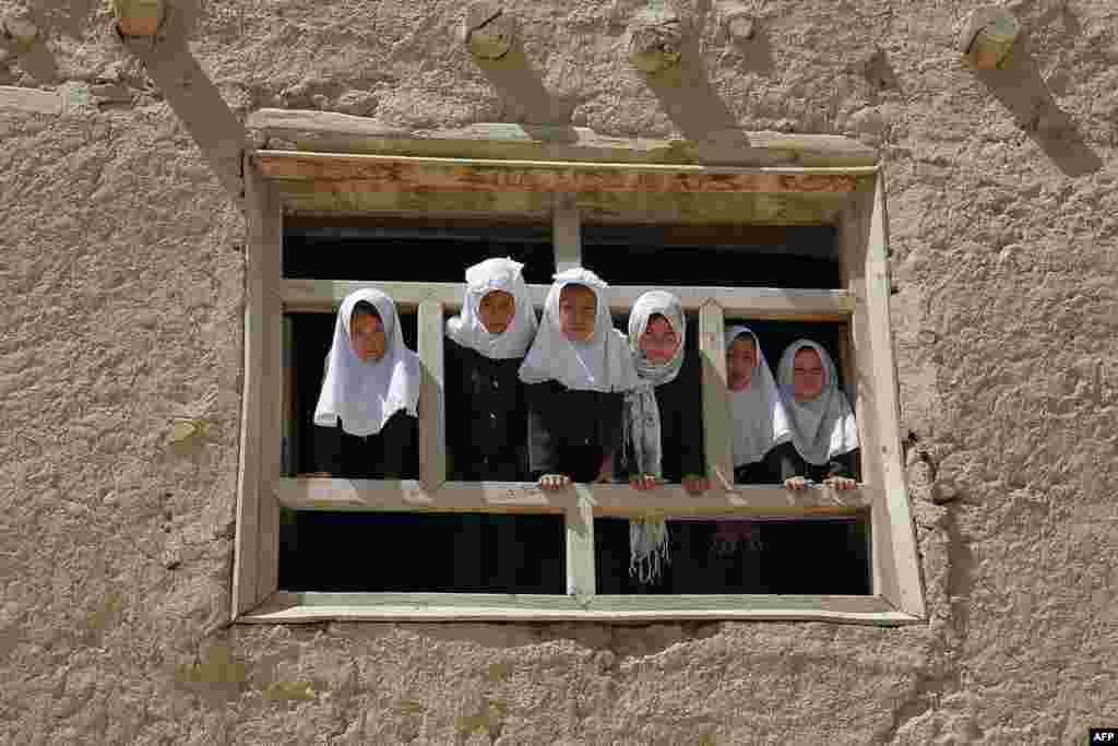 Afghan schoolgirls look out from a window of their school in Ghazni. (AFP/RahmatullahAlizada)