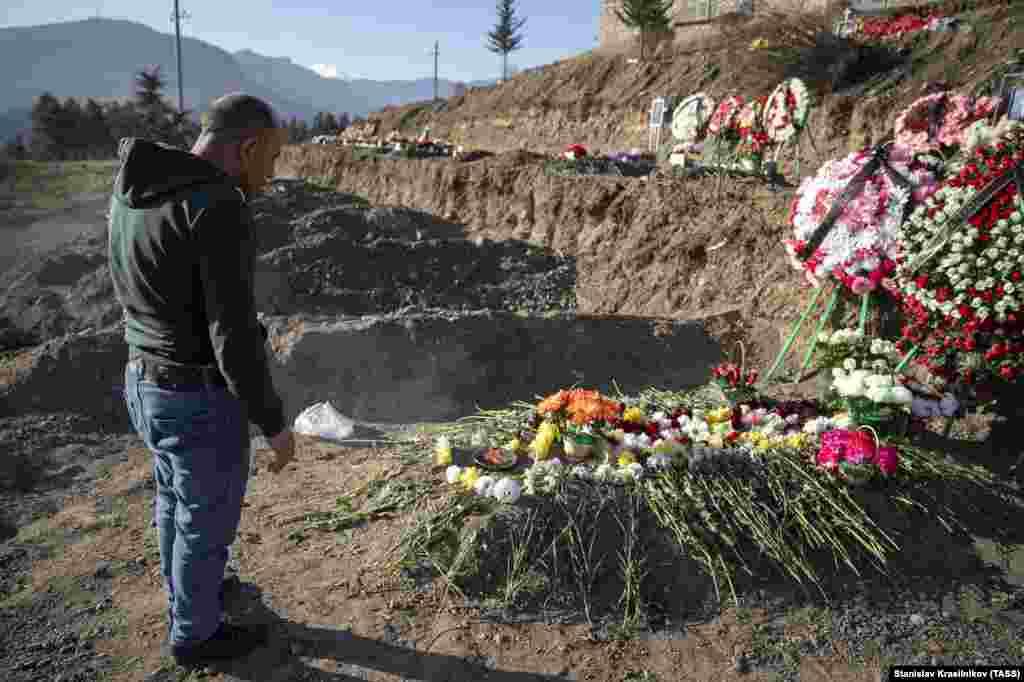 Мужчина у могилы своего сына в Степанакерте. 27 ноября 2020 года. Конфликт 2020 года, по официальным сообщениям, унес жизни 2 783 азербайджанских военнослужащих и 2 425 армянских солдат.
