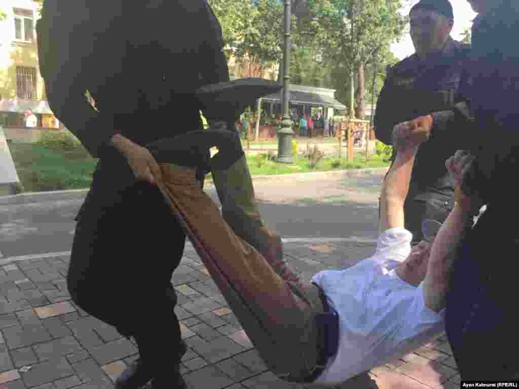 Полиция қызметкерлері көшеде ұсталған адамды көтеріп әкетіп барады.