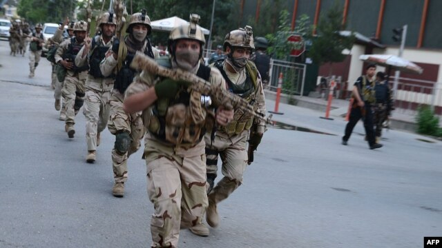 Afghan and international special forces run to the site of a clash between Afghan security forces and Taliban fighters in Kabul on May 24.