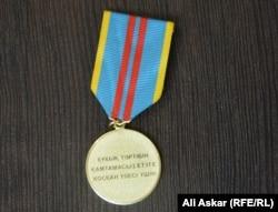Медаль «За вклад в обеспечение правопорядка», которой награжден Куаныш Карасартов, задержавший вооруженного боевика. Актобе, 30 августа 2016 года.