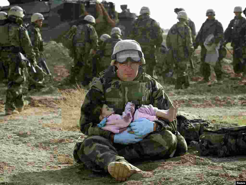 U.S. Navy Hospital Corpsman HM1 Richard Barnett, assigned to the 1st Marine Division, holds an Iraqi child in central Iraq in this March 29, 2003 file photo. Confused front line crossfire ripped apart an Iraqi family after local soldiers appeared to force civilians towards positions held by U.S. Marines. March 20 marks the one year anniversary of the beginning of the U.S. led war against Iraq. The war started on March 20 Baghdad local time, March 19 Washington D.C. local time. REUTERS/Damir Sagolj HIGHEST QUALITY AVAILABLE