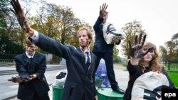 Demonstranți ecologiști deghizați în corporatiști protestează la Bruxelles îm marginea summitului climateric al Uniunii Europene.