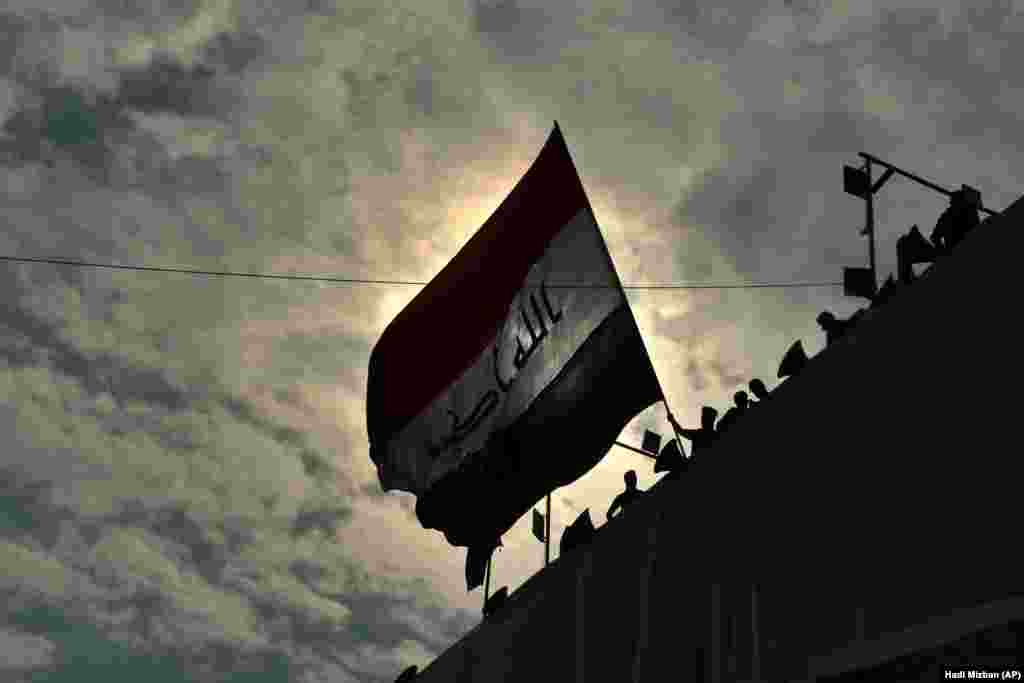 Anti-government protesters wave a flag while standing on a building near Tahrir Square in Baghdad, Iraq. (AP/Hadi Mizban)