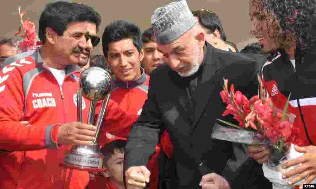 Afghan President Hamid Karzai congratulated members of the Afghan national soccer team at Kabul International Airport.