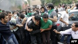 Прыхільнікі кандыдата ў прэзыдэнта Ірану Хасэйна Мусаві, які прайграў на выбарах, выводзяць пабітага паліцыяй у часе сутычак з паліцыяй. 13 чэрвеня. Тэгеран.