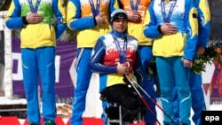 Ukrainian silver medalist Olena Iurkovska (front) and teammates cover their medals during the medal ceremony after the Cross Country 4 x 2.5-Kilometer Mixed Relay competition at Laura Cross-Country Ski & Biathlon Center during the Sochi Paralympic Games in a show of protest against events in their homeland, where Russian troops are occupying Crimea.