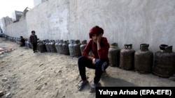 Yemenis wait next to empty cooking-gas cylinders for gas supplies amid increasing gas shortages in the capital, Sanaa, last month.