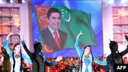 Түркмөн президенти Гурбангулы Бердымухаммедовдун сүрөтүнүн жанында бийлеп жаткан кыздар. Ашхабад.