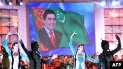 Девушки танцуют перед портретом президента Гурбангулы Бердымухамедова во время празднования исламского праздника Ид аль-Адха в Ашхабаде, 17 ноября 2010 года