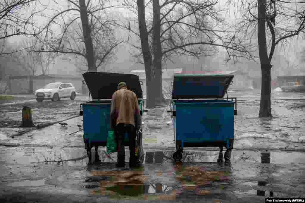 A man searches through a trash bin in a residential area.