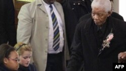 South African ex-President Nelson Mandela (right) arrives at a June 2010 memorial for a great-granddaughter killed in an car accident.