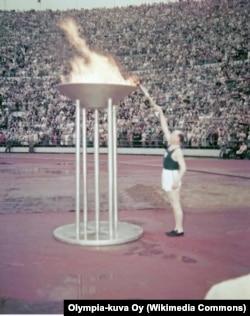 Финский бегун Пааво Нурми зажигает Олимпийский огонь на церемонии открытия летней Олимпиады 1952 года
