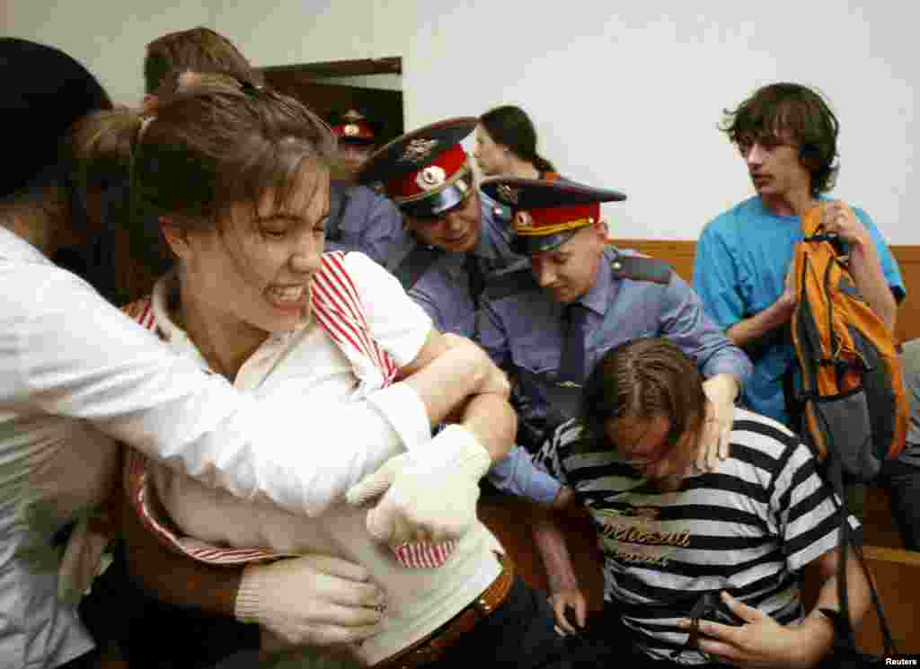 Police remove Nadezhda Tolokonnikova (left), Oleg Vorotnikov (bottom right), and other activists of the art group Voina from the court after they disrupted a hearing against the director of the Sakharov Center in Moscow in May 2009.
