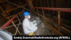 Кореспондент Радіо Свобода Євген Солонина сидить поруч з елементром конструкцій 4-го реактора, який викинуло сюди під час вибуху у 1986-му році