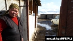 A woman surveys flood damage in Kyrgyzstan's Naryn region on March 29.