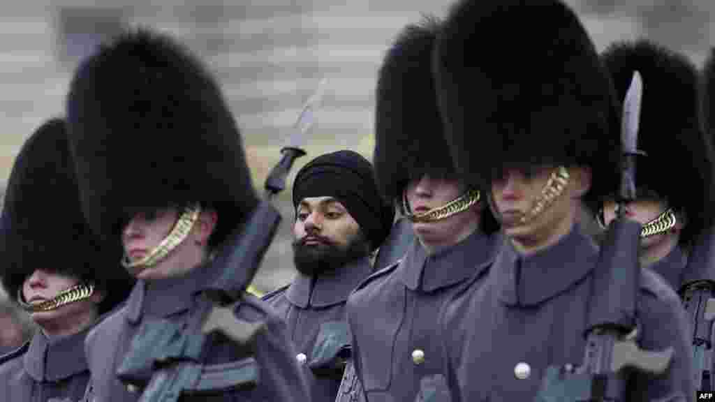 Sikh Scots Guards soldier Jatenderpal Singh Bhullar (center) marches past during a changing-of-the-guard ceremony outside Buckingham Palace in London. Bhullar became the first guardsman to parade outside Buckingham Palace wearing a turban instead of the traditional bearskin hat. (AFP/Carl Court)